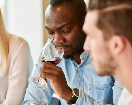 Cape Winelands has been producing fine wines and wineries in South Africa have won many awards for their world-class wine farms in Cape Town. Man is smelling wine and soaking in the wine tasting